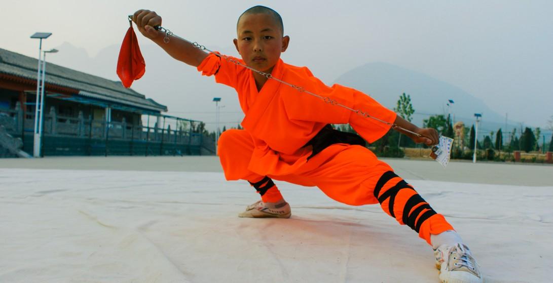 Młody adept Shaolin wykonuje formę z żelaznym łańcuchem Jiu Jie Bian